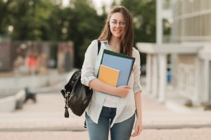 Portrait of a student girl with glasses. She stands in the background of the park and holds notebooks and folders in her hands. The girl is preparing to enter the university